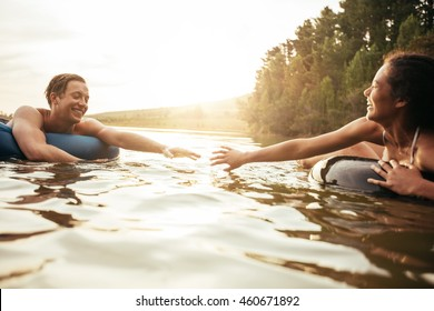 Affectionate young couple about to hold hands while floating on inner tubes in water. Young man and woman in an inflatable tube in a lake.