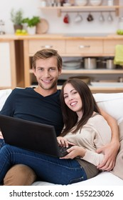 Affectionate young couple using a laptop computer as they relax together on a sofa in their living room