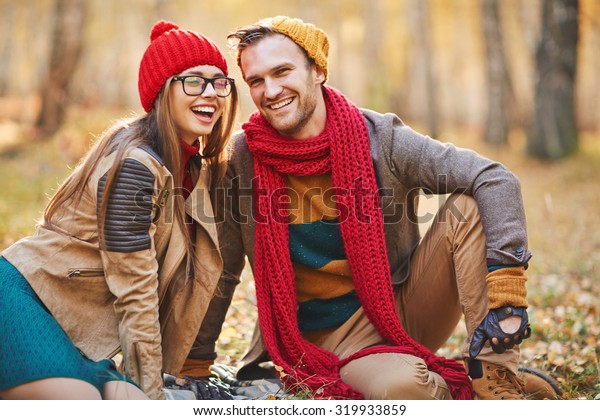 Affectionate young dates laughing during rest in park