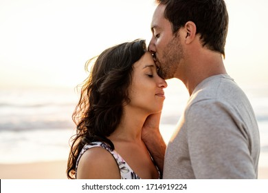 Affectionate young man kissing his wife on her forehead while standing together on a beach at dusk