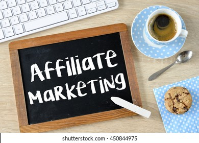 Affiliate marketing on Blackboard with chalk , keyboard,cup of coffee,cookie on table background