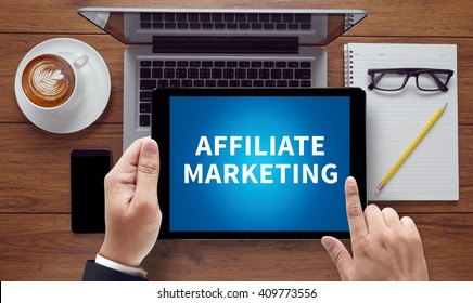 AFFILIATE MARKETING, on the tablet pc screen held by businessman hands - online, top view