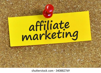 affiliate marketing word on yellow notepaper with cork background.