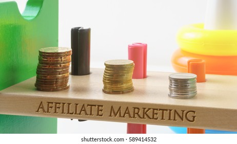 AFFILIATE MARKETING written on wood with golden and silver coins stacked with plastic toy bar on shallow DOF.Filter applied