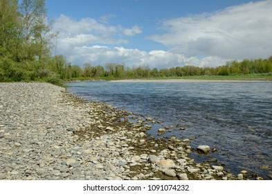 Affluent river deposits a point bar or a slip-off slope.
