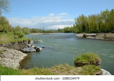 Affluent river erodes its cut bank on the left and deposits a point bar on the right.