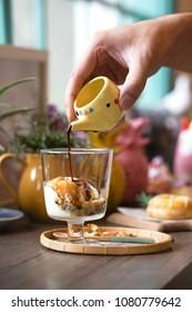 Affogato coffee with ice cream. Espresso shot and a scoop of vanilla ice cream. A hand pouring espresso into gelato ice cream.