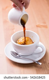 Affogato coffee with ice cream on a cup on wooden background