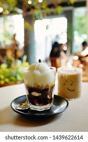 "Affogato, Italian coffee-based dessert with vanilla ice cream topped or ""drowned"" with a shot of hot espresso. Iced coffee and coffee shop blur background with bokeh image."
