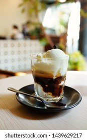 "Affogato, Italian coffee-based dessert with vanilla ice cream topped or ""drowned"" with a shot of hot espresso. Blur cafe interior background with bokeh image."