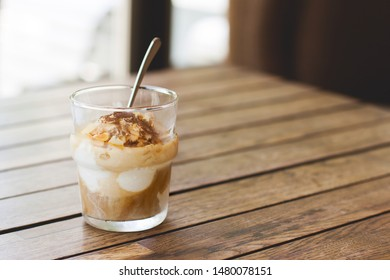 Affogato on a wooden table. Delicious espresso dessert with ice cream in a glass. Atmosphere of summer holidays, siesta, coffee breaks