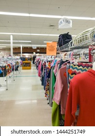 Affordable Used Clothing for Sale on hanging Racks at a Thrift or Resale Store