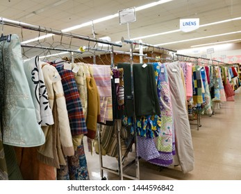 Affordable Used Linens and Household Items for Sale on hanging Racks at a Thrift or Resale Store