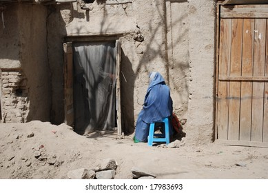 Afghan woman sits on chair
