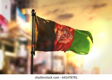 Afghanistan Flag Against City Blurred Background At Sunrise Backlight 3D Rendering