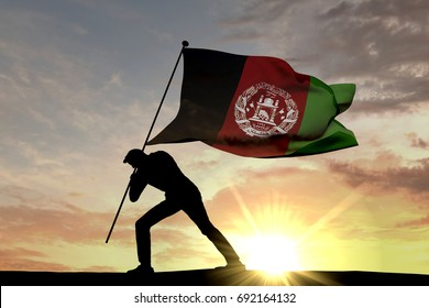 Afghanistan flag being pushed into the ground by a male silhouette. 3D Rendering