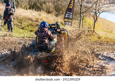 Afipsip, Russia - October 31, 2020: Sportsman on quad bike drives splashing in water at Mud Racing contest. ATV SSV motobike competitions are popular extreme sport and outdoor activity