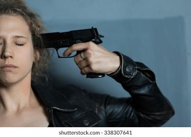 Afraid despair woman with gun committing suicide