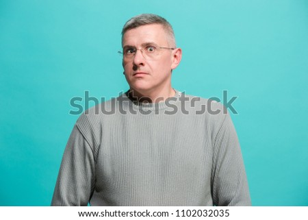 I'm afraid. Fright. Portrait of the scared man. Business man standing isolated on trendy blue studio background. male half-length portrait. Human emotions, facial expression concept. Front view