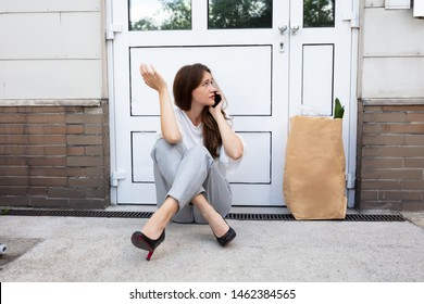 An Afraid Young Woman Sitting Outside The Door Talking On Mobilephone