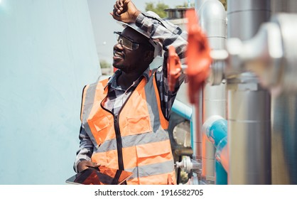 Africa American worker wearing safety goggles check condition of crude oil centrifugal pump and lube oil system. Metal lathe industrial manufacturing factory outside. Hard working concept - Shutterstock ID 1916582705