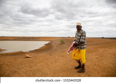 Africa, Kenya, Kenyan-Somali border -Man standing in front of the lake began to dry out of the water, causing water to smear the poor Kenyan villages - August 20, 2018,