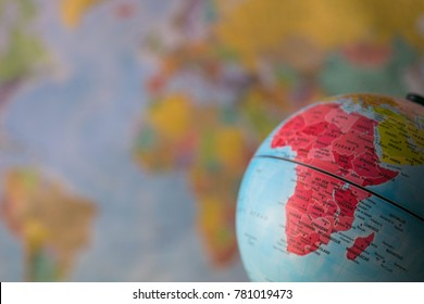 Africa map on a globe with earth map in the background.