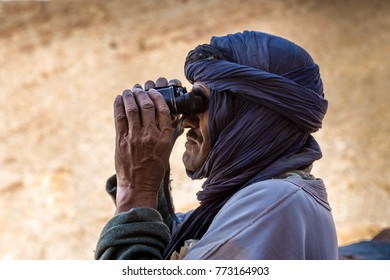 AFRICA, MOROCCO, REGION GUELMIM-OUED NOUN, SIDI IFNI PROVENCE - CIRCA MAR 2006 - Berber looking through binocular at Amtoudi