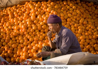 AFRICA, MOROCCO, REGION GUELMIM-OUED NOUN, SIDI IFNI PROVENCE - CIRCA FEB 2007 - Man eats an orange in front of a big pile of oranges at market in Guelmim