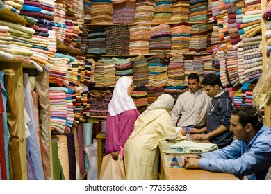 AFRICA, MOROCCO, REGION MARRAKESH-SAFI - CIRCA MAR 2006 - People negotiating in a Fabric shop in Souk at the city of  Marrakech
