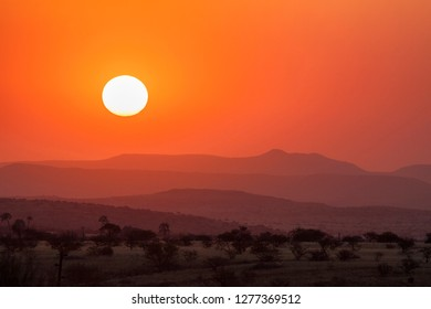 Africa, Namibia, Damaraland. Orange sunset over mountains.