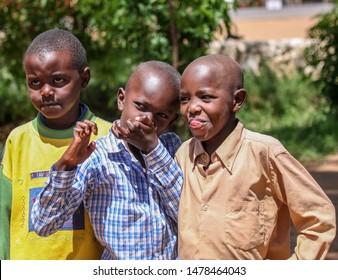 Africa. Tanzania. 06/15/2013. Photo of three Kenyan teens. Expression of anger, joy and threat.