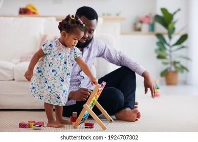 africam-amerikanische Familie, Vater und Tochter, die zu Hause mit Holzabacus und Spielzeug spielt