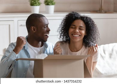 African 30s spouses sitting on sofa opening cardboard box feels excited and happy clients receiving long awaited carton package, fast post mail parcel delivery, reliable postal courier service concept
