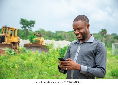 african agricultural businessman, using a mobile phone on a plot of land