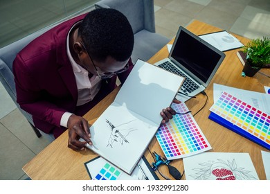 african americal stylish male in marsala jacket working in modern big office