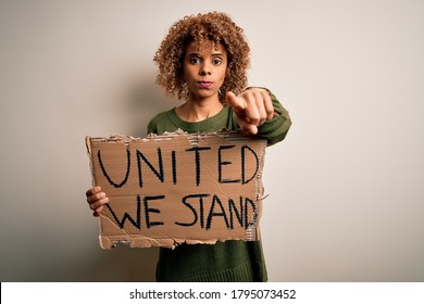 African american activist woman asking for unity holding banner with united stand message pointing with finger to the camera and to you, hand sign, positive and confident gesture from the front