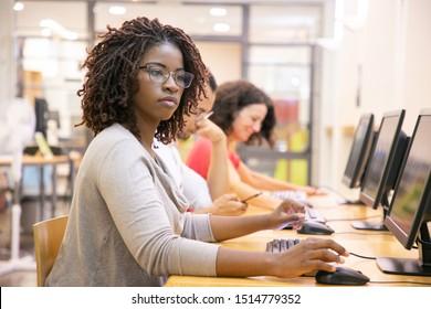 Afroamerikanischer Erwachsenenschüler, der im Computerunterricht arbeitet. Linie von Mann und Frau in Gelegenheitssitze am Tisch, mit Desktops, Schreibweisen. Ausbildungskonzept