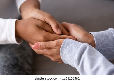 African american adult woman foster care parent single black mother holding hands of child teen daughter give support love protection, charity and adoption, family trust help concept, close up view