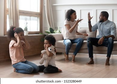 African american angry married couple arguing and shouting, while two mixed race upset stressed kids sitting on floor, closing ears hurt by parents fighting, family conflicts, divorce concept.