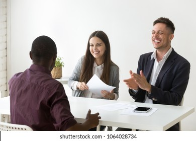 African american applicant make caucasian hr laugh at successful job interview, black candidate telling funny joke while talking to happy smiling recruiters, good first impression and hiring concept