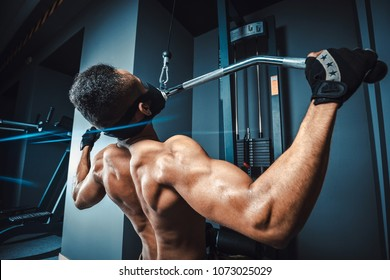 african american athletic man doing exercise in pull down machine back view. black fitness man working out lat pulldown training at gym.