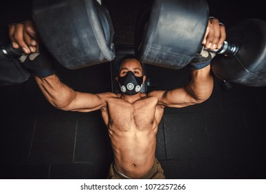 african american athletic man in mask lifting dumbbells and working on his chest view from above. black man in gym doing exercise for chest with dumbbells close-up