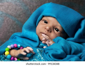 African American Baby Doll Portrait lying under turquoise blanket