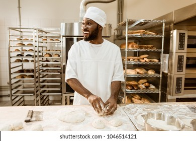 african american baker preparing raw dough for pastry on baking manufacture