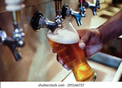 African American bartender filling beer glass from a bar tap