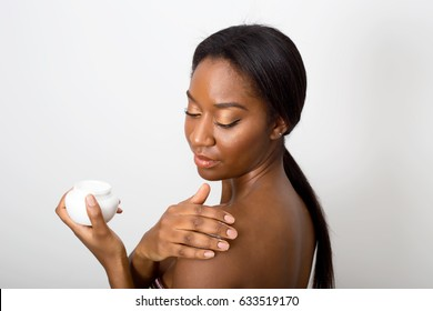 african american beauty applying moisturizing cream