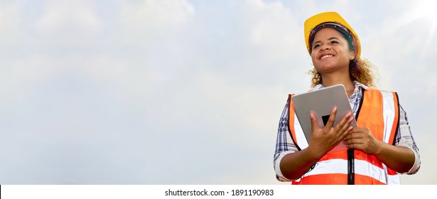 African American black female engineer or architect stands outdoors with tablet.
