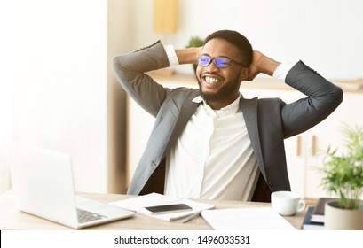 African American boss leaning back in chair, resting from office work. Copy space