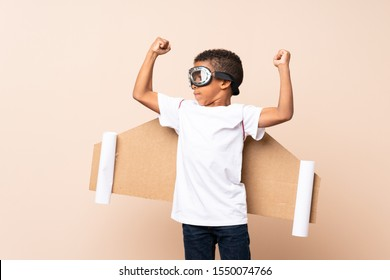 African American boy  with aviator hat and with wings and making strong gesture over isolated background